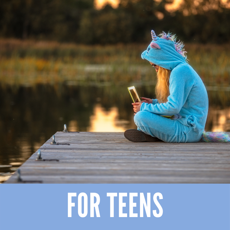 Teen wearing unicorn costume reading iPad