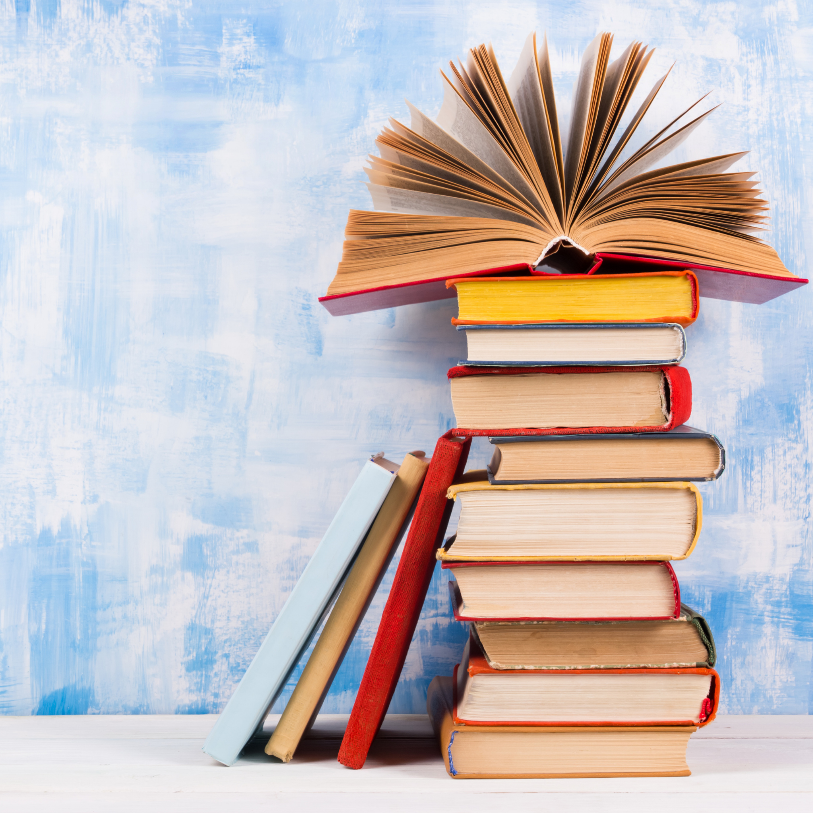 a stack of books in front of a blue background with the top book open