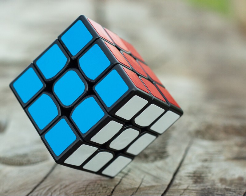 Boredom Busters - Completed Rubik's cube standing on a point, showing just the blue, white, and red sides