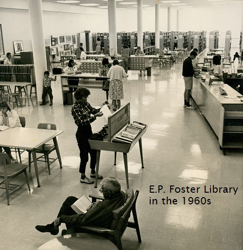 Black and white photo of the E.P. Foster Library in the 1960s. Shows card catalogs, a long reference desk, book stacks, and tables. About 14 people are shown in the photo.
