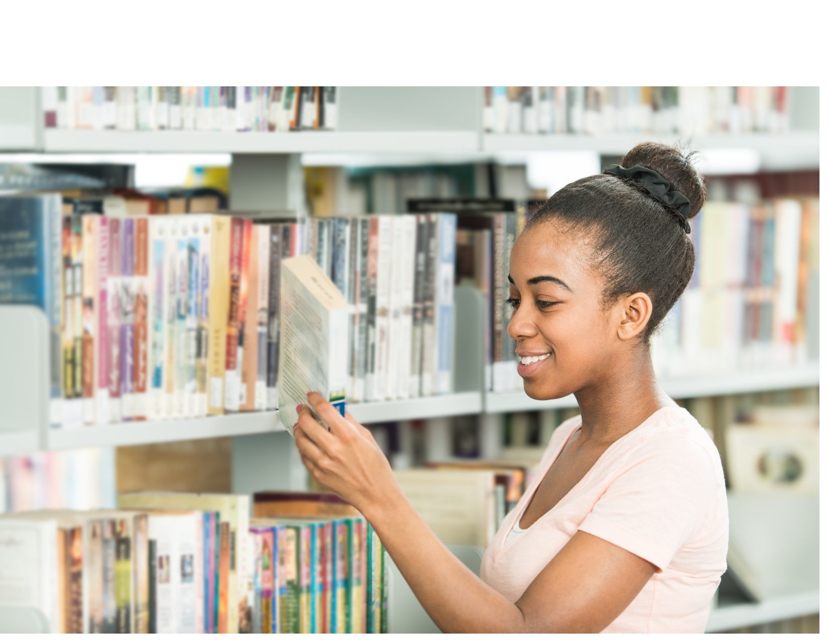 Young girl browsing the library shelf and selecting a book