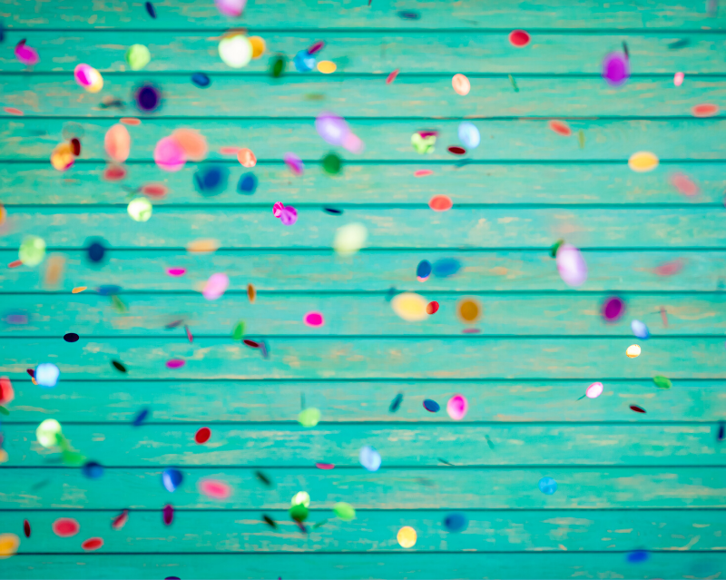 colorful confetti falling in front of a turquoise wood wall