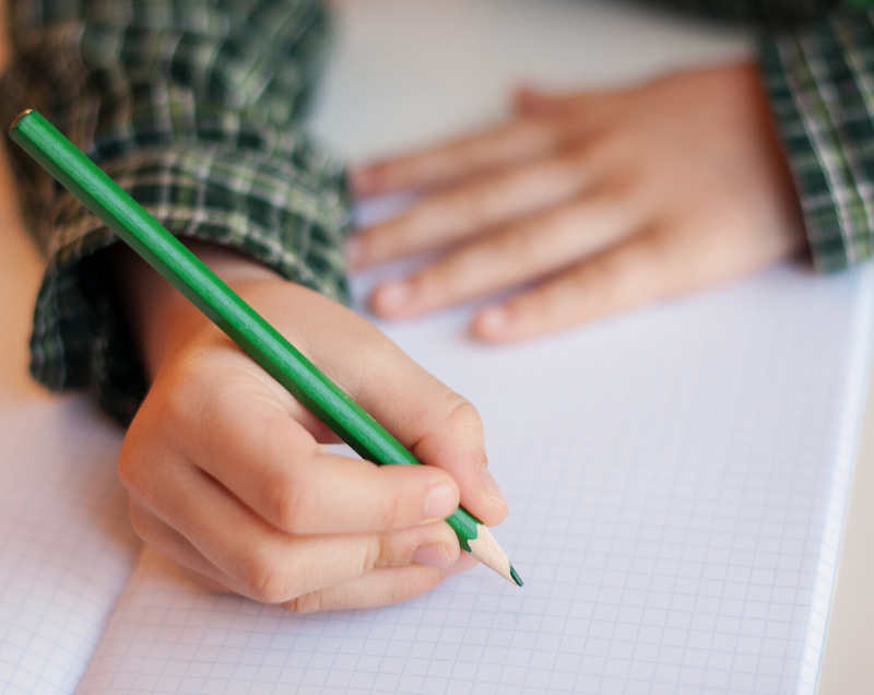 a young person's hands, one holding a pencil over paper