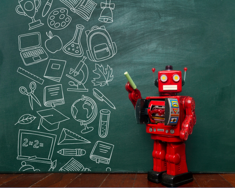 Red robot in front of school blackboard with chalk picture drawings
