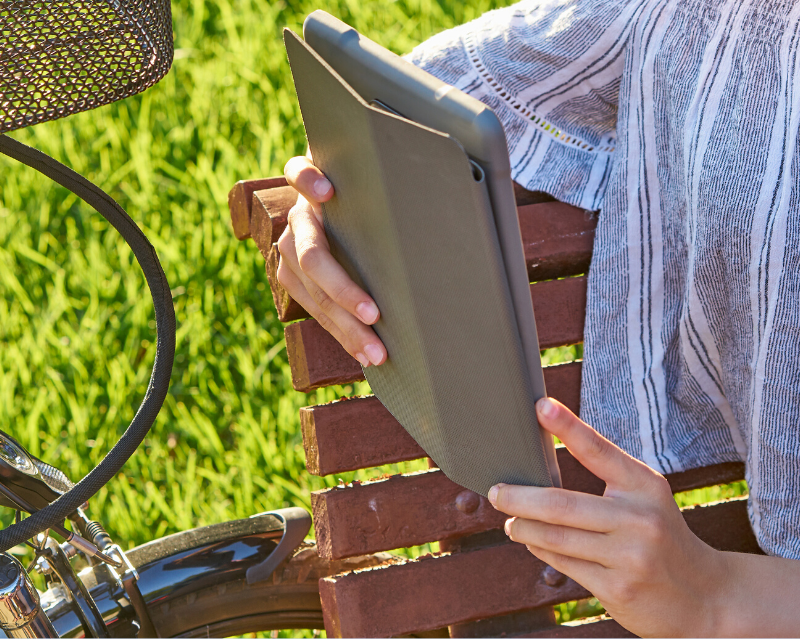 Teen reading on a tablet while sitting on a park bench with a bicycle nearby