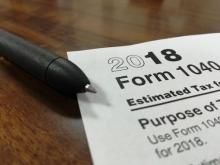 Photograph of 1040 tax form and stapler on table